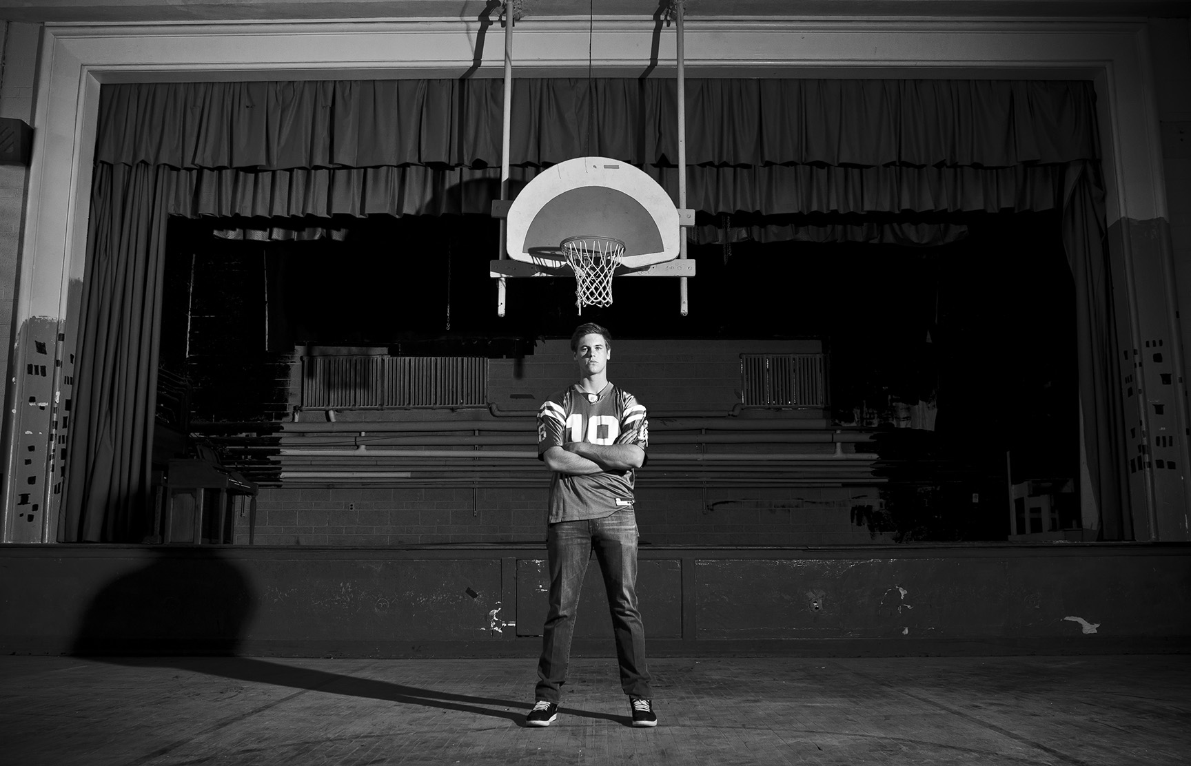 Senior photo in front of basketball hoop in a gym
