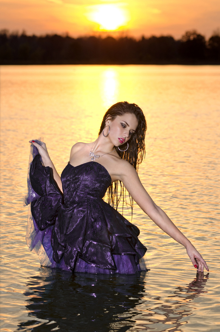 senior in prom dress standing in lake michigan